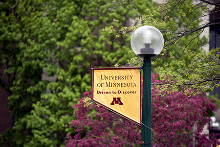 UMN campus signage with spring foliage